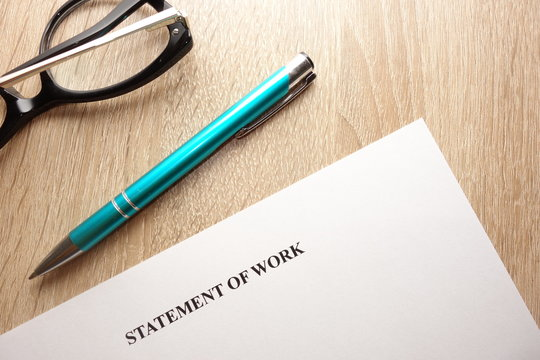 Statement of work, pen and eyeglasses on desk