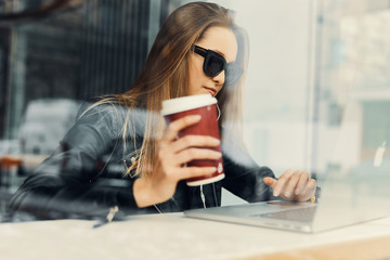Young girl sit in coffee place in front of the window look at her laptop and drink tea from red cup
