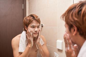 Portrait of an asian man washing in bathroom