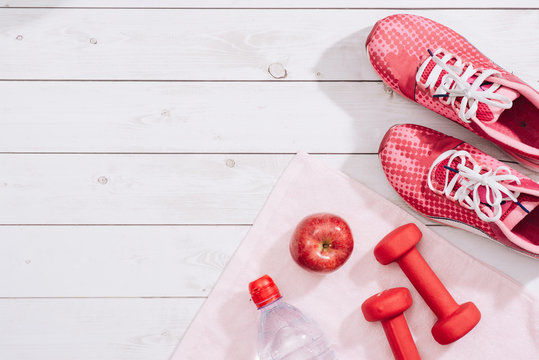 fitness concept with dumbbells and red apple - sport and leisure