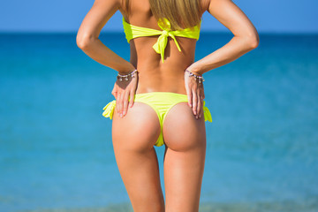beautiful fit young woman butt in sexy yellow bikini at the beach and blue sea