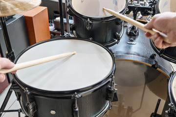 Two hands beat into a drum