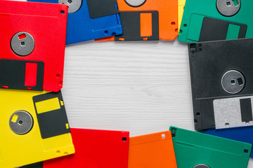 Vintage multi-colored floppy disk on white background. Flat lay copyspace.