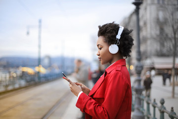 Girl listening music in the street while waiting the train