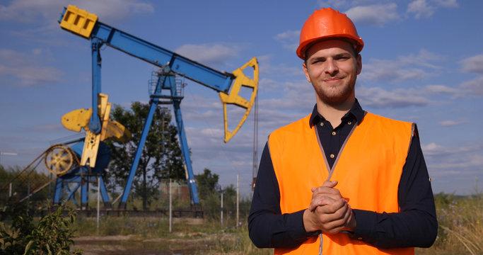 Happy Handsome Engineer Man Employee Presentation near Oil Pump Field or Gas Deposit Industrial Area