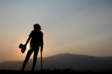 silhouette of girl standing alone and hand holding teddy bear at a sunset time