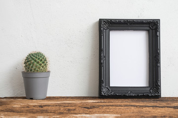 Black photo frame on old wooden table with cactus over white concrete wall background