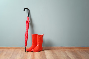 Stylish red umbrella and rubber boots indoors