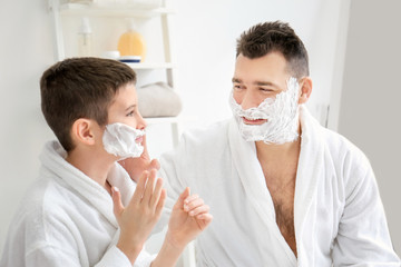 Dad teaching his son to shave in bathroom