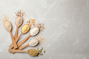 Spoons with different types of flour on light background