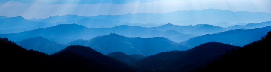 Beautiful landscape of blue mountains layers during sunset with sunrays