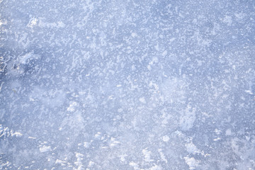ice background made of frozen lake with beautiful pattern and bluish colortone