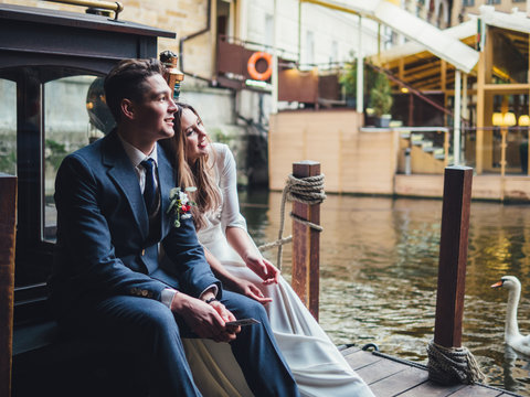 Groom and bride in docks of river bus. winter wedding in Prague