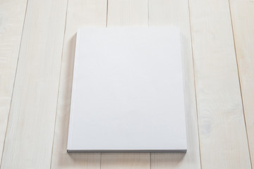 Blank book cover mockup template with page front side on white surface on wood table