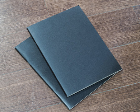 Black dark blank leather magazine cover book template on white grey wooden table background