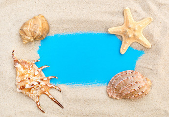 Frame from sand and seashells on blue background.