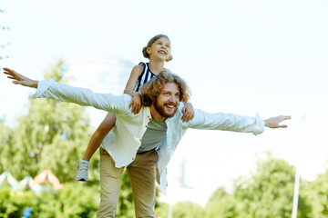 Young man with outstreched arms and little daughter on his back enjoying summer day in park