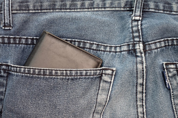Behind the jeans with a wallet inside.