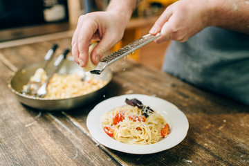 Chef grates cheese in to the plate with fettuccine