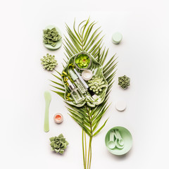 Homemade skin care setting . Herbal cosmetic mask making. Tropical leaves and succulents with cosmetic products and accessories: Mask Brush, bowl, spatula, measuring spoons on white desktop background