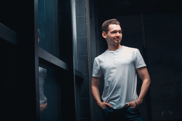 Handsome businessman in white t-shir, stands by the window and looks away. A young man looks like an executive director or head of a company or enterprise. Room in loft style.