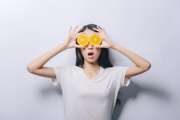 Studio portrait of young surprised funny girl holding two orange slices in t-shirt on white background and smiling. Fresh fruits and healthy diet concept. Free copy space provided