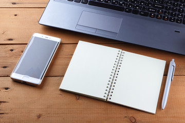 Laptop on a wooden background, a job on an old table, a smartphone and a notebook, a pen and glasses in the workplace, copy Space, office space in a minimalist style, the place for designer