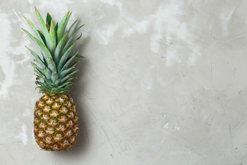 Whole pineapple fruit on grey concrete background