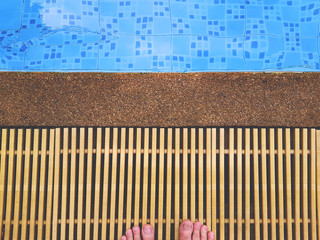 High Angle View of Barefoot Standing by the Swimming Pool