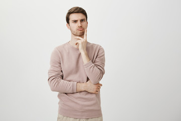 Portrait of unhappy determined european male with bristle touching chin while thinking and looking with serious and worried look at camera, standing against gray background. Dad make up punishment