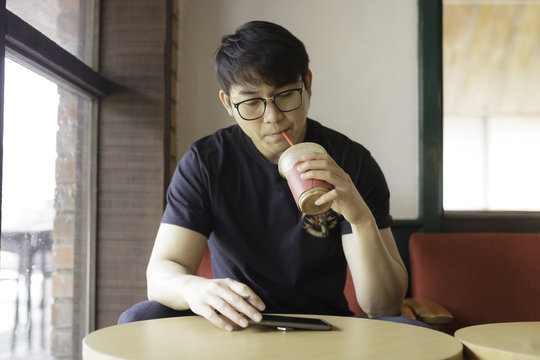 asian man drinking  iced coffee and using smart phone