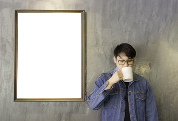 man drinking coffee cup and blank frame picture on wall background