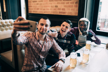 Multiracial friends group in casual clothes are smiling, taking selfie and drinking beer while sitting in pub