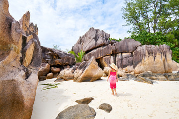female tourist admires beautiful granite rocks on curieuse island, praslin, seychelles island