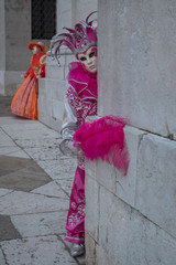 Woman dressed up as jester in pink costume posing at the San Giorgio Maggiore Church on San Giorgio island during the Venice Carnival. Another mask is in the background.