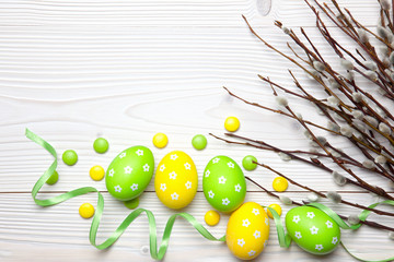Easter eggs and willow branches on wooden background.