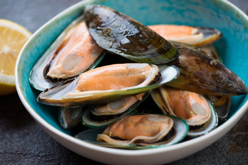 Black bowl with raw kiwi mussels, close-up, selective focus, horizontal shot
