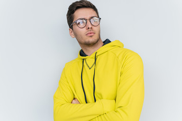 Studio portrait of thoughtful blond man wearing yellow hoodie and trendy glasses, looks pensively aside, thinks about his plans, posing on white wall background. People and emotion concept.