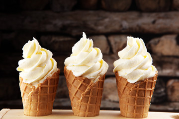 Vanilla frozen yogurt or soft ice cream in waffle cone.
