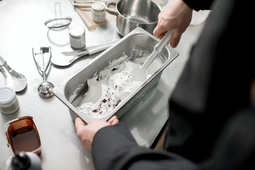 Chef mixing ice cream with chocolate in the metal tray on the kitchen