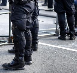 Polizisten in schwarzer Uniform hinter der Absperrung zu einer Demo