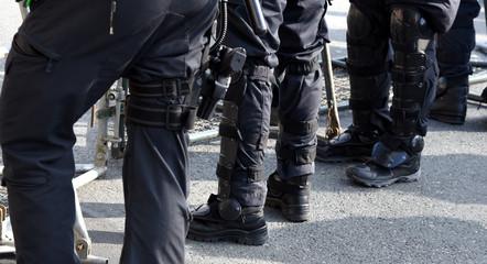 Polizisten in schwarzer Uniform und voller Ausrüstung im Einsatz auf einer Demo