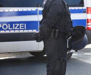 Polizist mit Uniform und Helm vor einem Einsatzfahrzeug