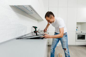 Young repairman installing induction cooker in kitchen