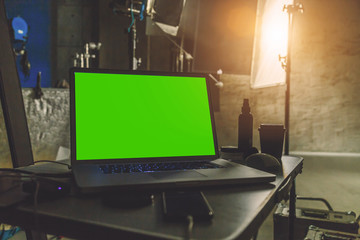 laptop with a green screen  on a table in production studio close up