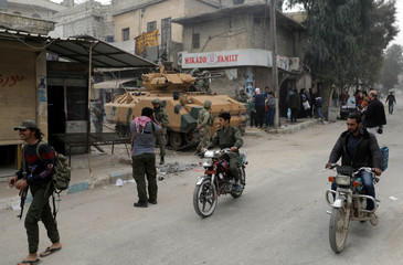 Men ride motorcycles as Turkish soldiers are seen with their military vehicle in the center of Afrin