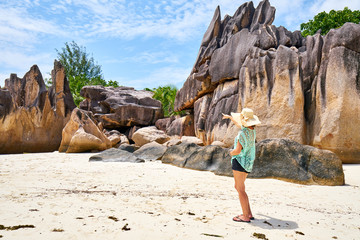 female tourist is walking on Laraie Bay's beach with granite rock, curieuse island, seychelles