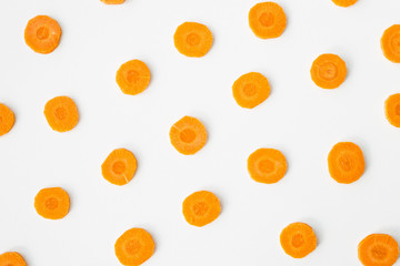 Bright round ringlets of carrots on a white background. Healthy food concept. Top view, flat lay