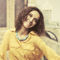Happy young fashion woman in yellow shirt walking in city street