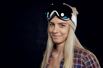 Snowboarding, extreme and adrenaline concept. Picture of beautiful young woman snowboarder with blonde hair posing in studio, wearing goggles, being happy, going to snowboarding spot with friends